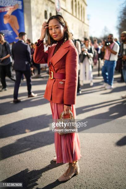Aimee Song wears a red blazer jacket a large belt a Lady Dior snake print bag a pink pleated skirt outside Dior during Paris Fashion Week Womenswear...