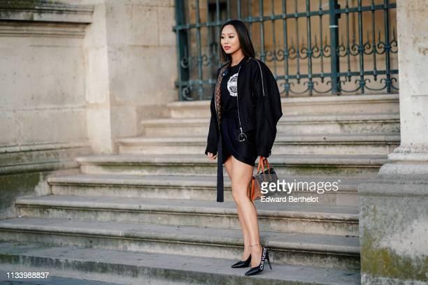 Aimee Song wears a Vuitton jacket with brown monogram inner lining a black skirt a Vuitton bag shoes a Vuitton top outside Louis Vuitton during Paris...