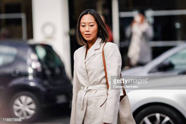 Aimee Song wears a white blazer jacket a bag white pants outside Elie Saab during Paris Fashion Week Womenswear Fall/Winter 2019/2020 on March 02...