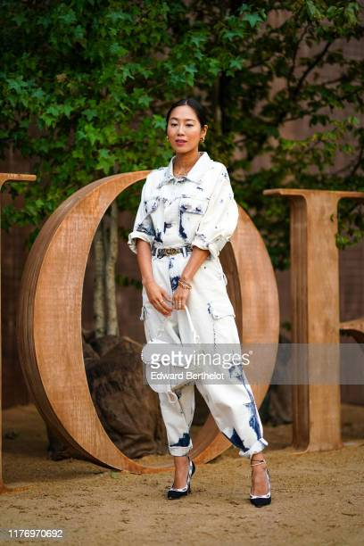 Aimee Song wears a white denim shirt with blue printed features a white Saddle bag from Dior Dior pointy shoes earrings outside Dior during Paris...