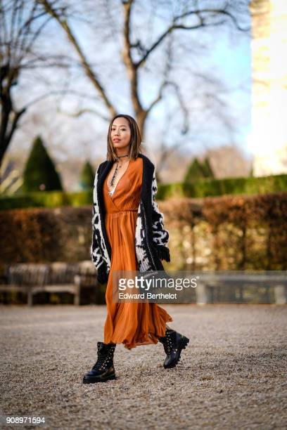 Aimee Song wears an orange dress after Dior during Haute Couture Spring/Summer 2018 on January 22 2018 in Paris France