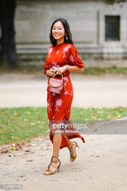 Aimee Song wears earrings bracelets a red puff sleeves sideslit long dress with white floral print a brown crocodile pattern Chloe bag crocodile...