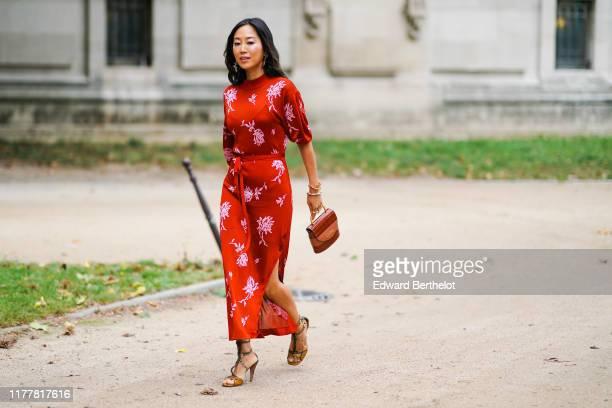 Aimee Song wears earrings, bracelets, a red puff sleeves side-slit long dress with white floral print, a brown crocodile pattern Chloe bag, crocodile...