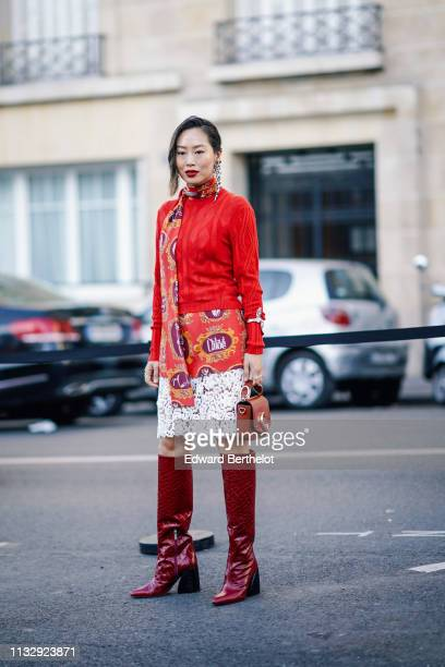 Aimee Song wears long earrings a red wool pullover a floral print scarf a Chloe skirt with white lace burgundy high leather boots a Chloe bag outside...