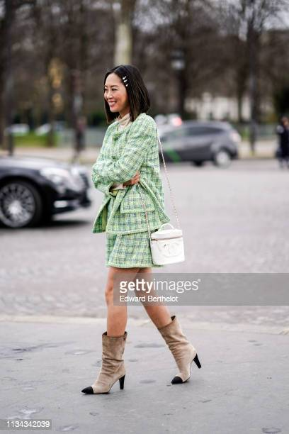 Aimee Song wears pearl hairpins a white turtleneck a green checkered tweed Chanel jacket with a skirt a white Chanel bag beige and black Chanel...