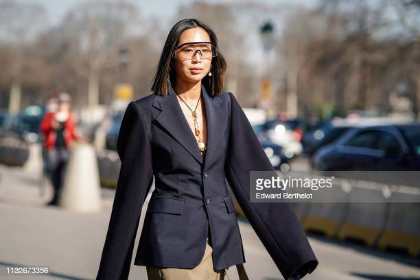 Aimee Song wears sunglasses an oversized blazer jacket a beige skirt Vuitton shoes a necklace earrings outside Maison Margiela during Paris Fashion...