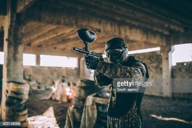 aiming with a paintball gun - metralhadora imagens e fotografias de stock