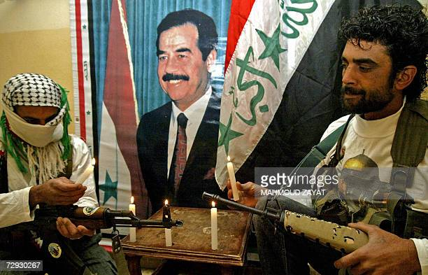 Armed Palestinian militants light candles near a poster of Iraqi executed leader Saddam Hussein during a symbolic funeral 05 January 2007 at the...