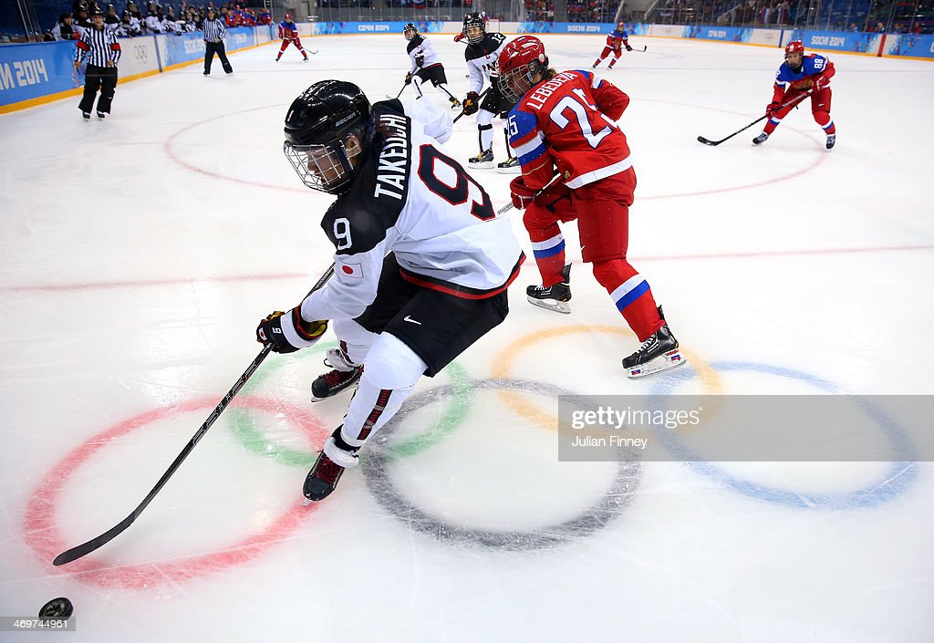 Aina Takeuchi #9 of Japan handles the puck against Yekaterina Lebedeva #25 of Russia in the third period during the Women's Ice Hockey Classification game on day nine of the Sochi 2014 Winter Olympics at Shayba Arena on February 16, 2014 in Sochi, Russia.