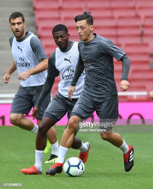 Ainsley MaitlandNiles and Mesut Ozil of Arsenal during a training session at Emirates Stadium on August 11 2018 in London England