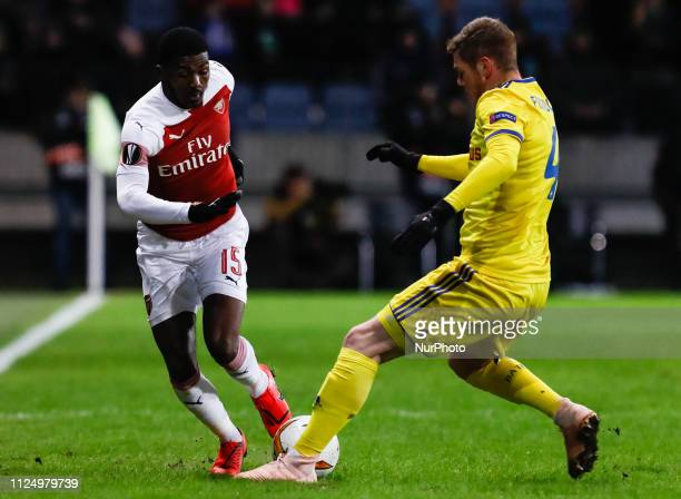 Ainsley MaitlandNiles of Arsenal and Aleksandar Filipovic of BATE Borisov vie for the ball during the UEFA Europa League Round of 32 first leg match...