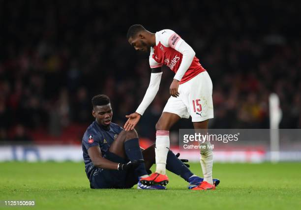 Ainsley MaitlandNiles of Arsenal offers his hand to Paul Pogba of Manchester United during the FA Cup Fourth Round match between Arsenal and...