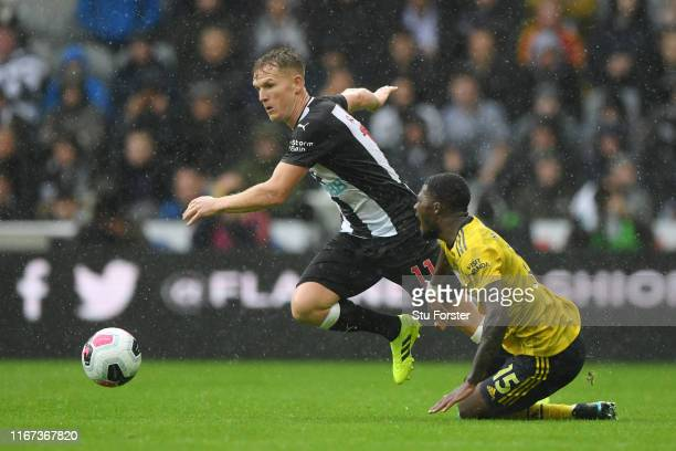 Ainsley Maitland-Niles of Arsenal tackles Matt Ritchie of Newcastle United during the Premier League match between Newcastle United and Arsenal FC at...