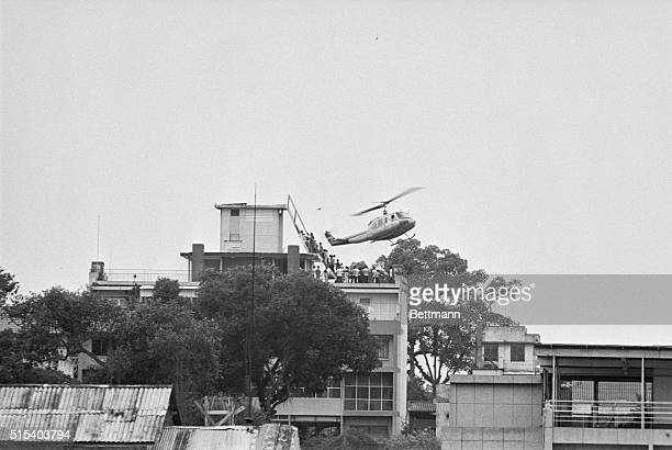 Air America helicopter crewman helps evacuees up the ladder on top of a Saigon building The evacuation side is one of many in the downtown area from...