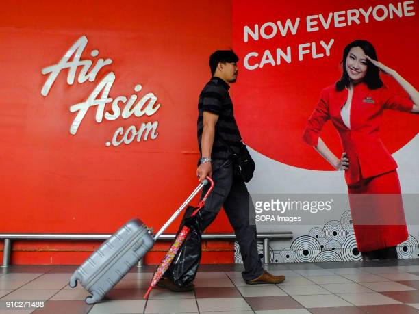 Air Asia commercial sign is seen at Kuala Lumpur while a man pulling his holiday baggage Kuala Lumpur or commonly known as KL is the national capital...