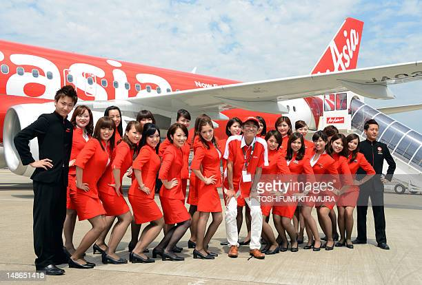 Air Asia Japan President Kazuyuki Iwakata and his company's cabin attendants wave during a photo session with newly designed Airbus A320 at the...
