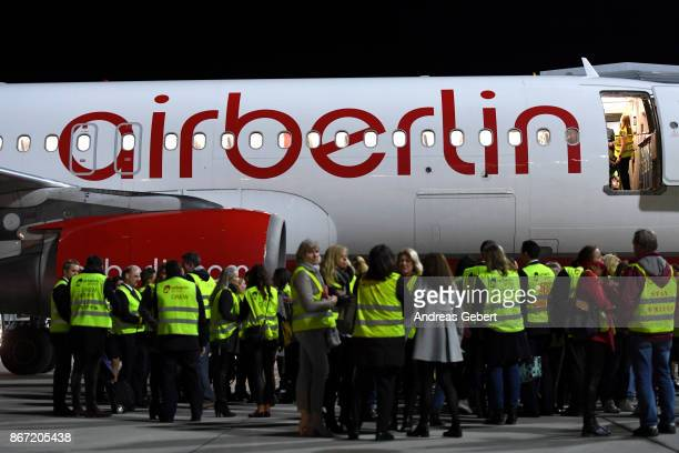 Air Berlin employees stand in front of Air Berlin flight AB 6210 before departing for Berlin at Munich International Airport on October 27 2017 near...