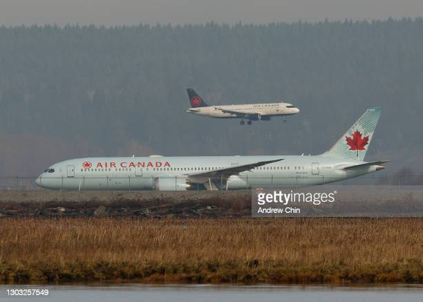 Air Canada flight AC7151 to Seoul taxis on the runway while Air Canada flight AC551 from Los Angeles lands at Vancouver International Airport on...
