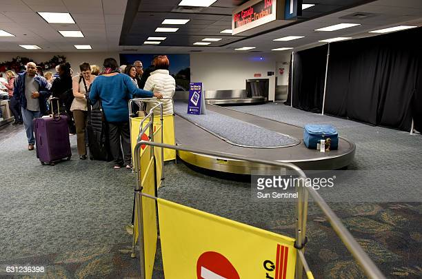Air Canada passengers wait to pick up their luggage at the partially opened Terminal 2 where Friday's fatal shooting took place at Fort...