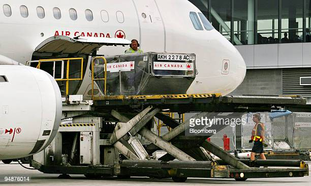 Air Canada workers unload cargo containers on the tarmac of Pearson International Airport in Toronto Ontario Canada Wednesday June 8 2005