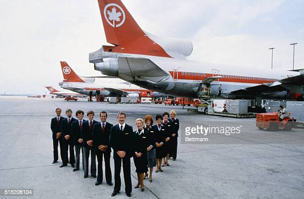 Air Canada's uniformed air crew stands in vform in front of one of its jumbo jets