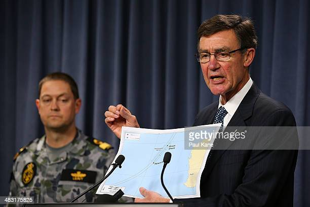 Air Chief Marshal Angus Houston holds a map outlining the current search areas of naval ships Ocean Shield and Haixun 01 during a press conference...