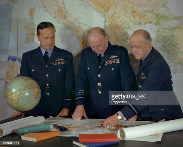 Air Chief Marshal Sir Frederick Bowhill Air Officer Commanding RAF Transport Command pictured in centre standing at a desk with A/C Brackley and A/C...