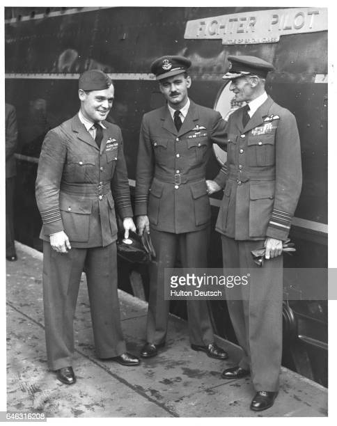 Air chief marshal Sir Keith Part stands with group captain Douglas Bader and a fellow officer on a railroad platform