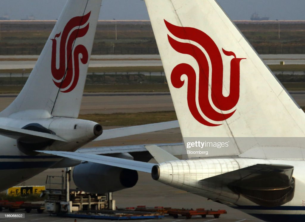 Air China Ltd. aircraft stand parked at Shanghai Pudong International Airport in Shanghai, China, on Saturday, Oct. 26, 2013. Airline profits worldwide in 2013 will be 7.9 percent smaller than estimated at $11.7 billion amid sluggish travel demand and rising oil prices tied to the Syria crisis, the International Air Transport Association said last month. Photographer: Tomohiro Ohsumi/Bloomberg via Getty Images