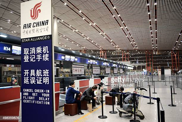 Air China's passengers wait for their flights at the Beijing Capital International airport after heavy snowstorm cancelled and delayed numerous...