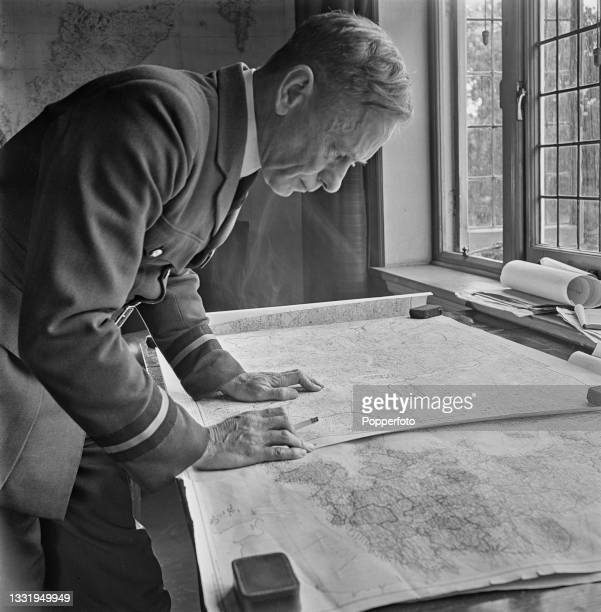 Air Commodore John Adrian Chamier of the Royal Air Force , founder and Commandant of the Air Training Corps, studies a map at ATC Headquarters in...