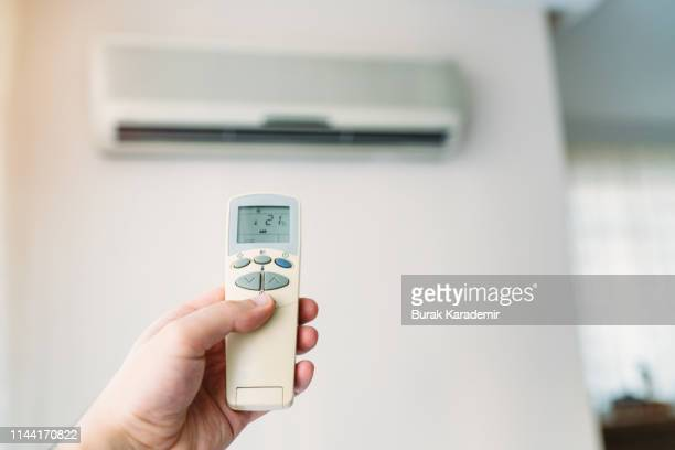 air conditioner closeup hand with remote control - air conditioner stock pictures, royalty-free photos & images