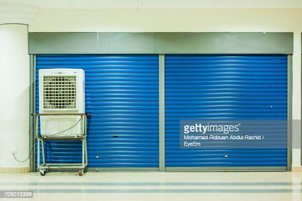 Air Conditioner On Trolley Against Closed Blue Shutters