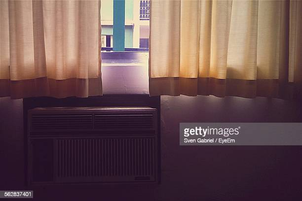 Air Conditioner On Wall With Curtains In Room