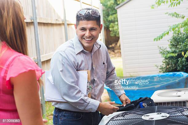 air conditioner repairman talking to homeowner while inspecting unit - building contractor stock pictures, royalty-free photos & images