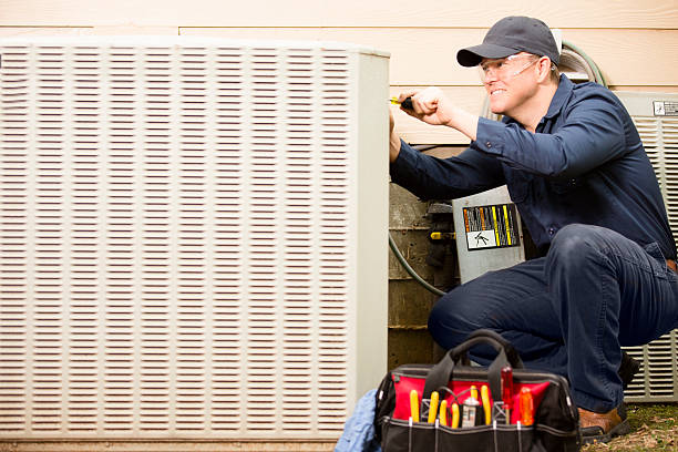 air conditioner repairman works on home unit. blue collar worker. - air conditioner stock pictures, royalty-free photos & images