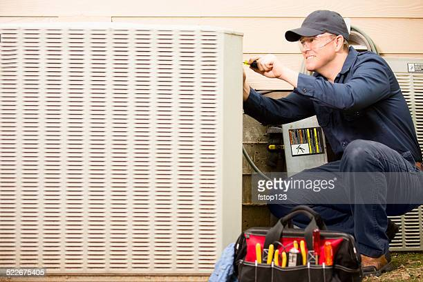 air conditioner repairman works on home unit. blue collar worker. - ventilator stock pictures, royalty-free photos & images