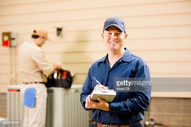 air conditioner repairmen work on home unit. blue collar workers. - inspector stock pictures, royalty-free photos & images