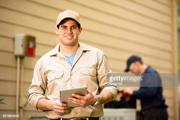 air conditioner repairmen work on home unit. blue collar workers. - air conditioner stock photos and pictures