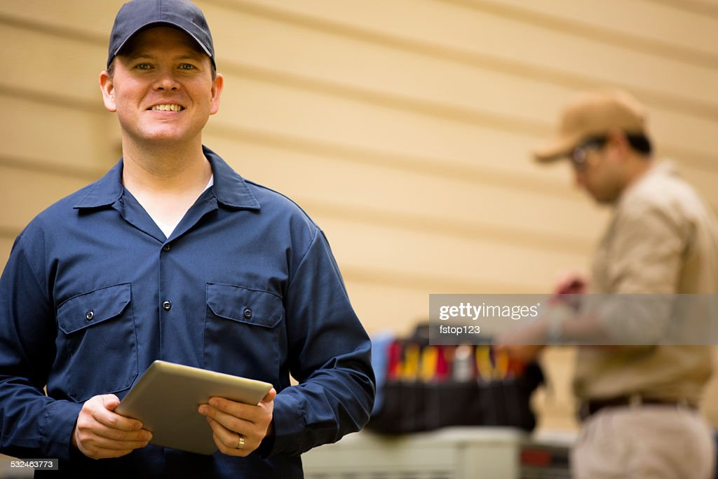 Air conditioner repairmen work on home unit. Blue collar workers. : Stock Photo