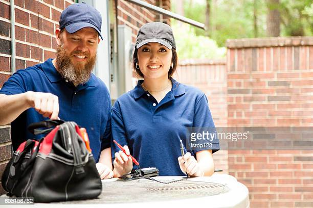 air conditioner repairmen work on home unit. - ventilator stock pictures, royalty-free photos & images