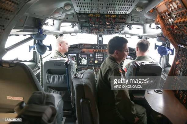 Air crew members stand in the cockpit of a Boeing E-3A Airborne Warning & Control System aircraft, at the Melsbroek Air Base, on November 27, 2019. -...