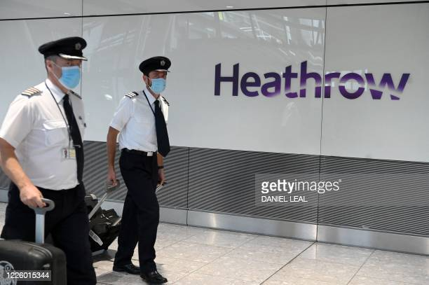 Air crew wearing a face mask or covering due to the COVID-19 pandemic, arrive at Heathrow airport, west London, on July 10, 2020. - The British...