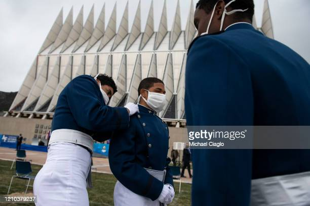 Air Force Academy cadets help each other update their uniforms with their new ranks after their graduation ceremony on April 18 2020 in Colorado...