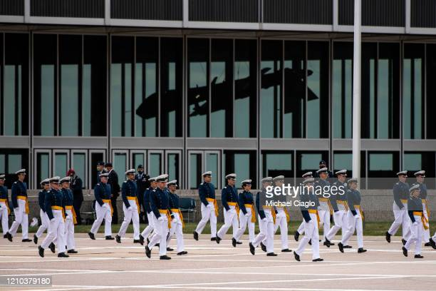 Air Force Academy cadets spaced eight feet apart march past a drone into their graduation ceremony on April 18 2020 in Colorado Springs Colorado...