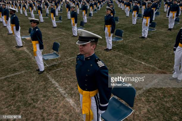 Air Force Academy cadets stand up to take an oath during their graduation ceremony on April 18 2020 in Colorado Springs Colorado Saturday's...