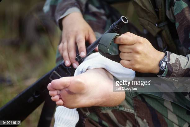 Air Force airman treats a blister on her foot during training at the US Army's Infantry training center Fort Dix New Jersey 1998