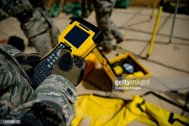 U.S. Air Force Airman uses a satellite base station to collect data on terrain features and distances.