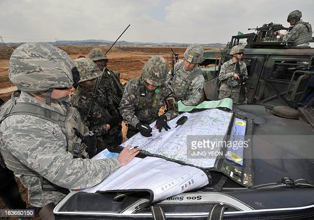 US Air Force and South Korean Army soldiers read maps for an operation to guard a US airbase as part of annual joint exercises outside the airbase in...