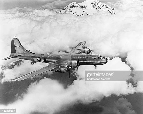 Air Force Boeing B-29 Superfortress bomber flying above the clouds and mountains, mid 1940s.